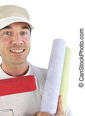 Man holding rolls of wallpaper