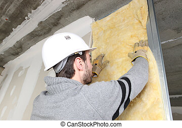 Laborer laying glass wool