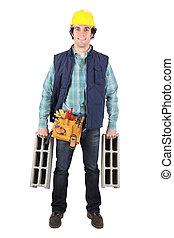 Smiling mason carrying cinder blocks