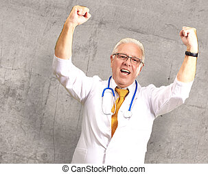 Senior Male Doctor In A Winning Gesture - Senior Male Doctor...