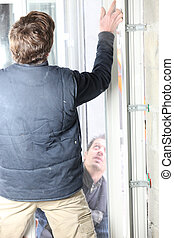 Two men fitting a new window