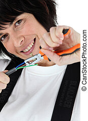 Woman pulling wires using a pair of pliers