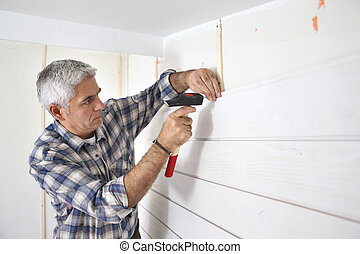 Grey-haired man replacing house paneling