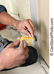 Worker with yellow adhesive tape