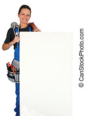 Female plumber with tools of the trade and a large board left blank for your message