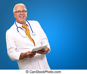 Portrait Of A Male Doctor Holding A Tab On Blue Background