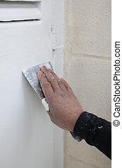 Man sandpapering wooden shutter