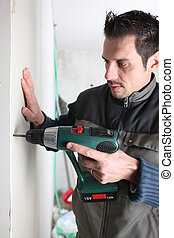 Man drilling into a wall