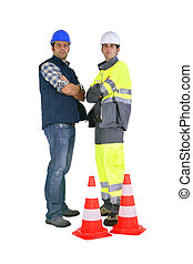 Two road workers stood by traffic cones