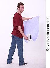 Young decorator installing wallpaper