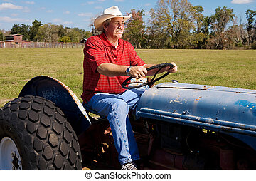 Cowboy on Tractor - Handsome mature cowboy riding his...