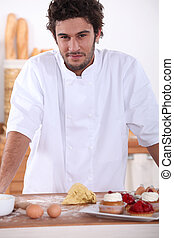 Male baker making sweet cakes
