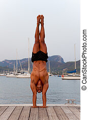 hand stand man - fit healthy strong man doing balance hand...