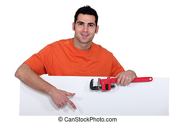 Man stood with wrench and poster