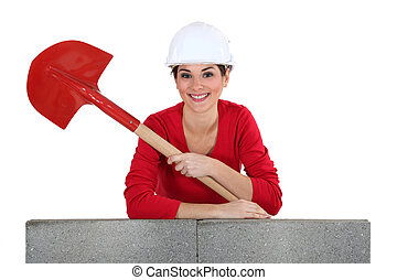 Girl with shovel leaning on a brickwall