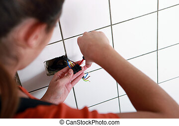 Female electrician wiring a wall socket