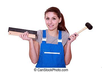 female worker holding hammer