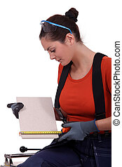 Tradeswoman measuring a tile