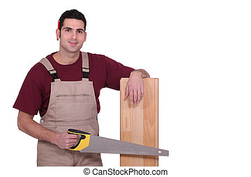 Carpenter with floorboards and a handsaw