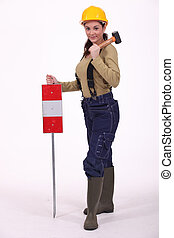 Woman with hammer over her shoulder signaling
