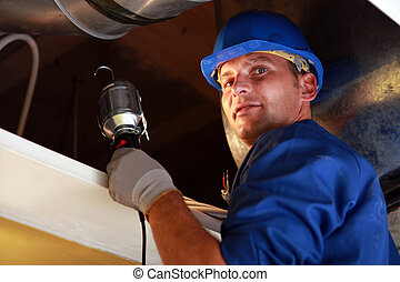Electrician looking into a loft space with a lamp