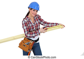 Female carpenter measuring a piece of wood.