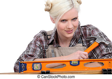 handywoman wearing a checked shirt and holding a hammer...