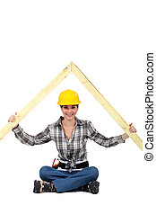 Female builder with a timber roof apex