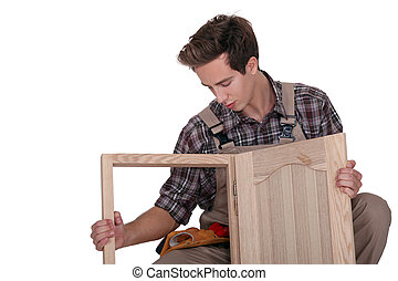 young cabinetmaker making cupboard