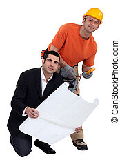 Tradesman standing beside an engineer