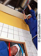 Tradespeople installing tubes