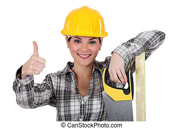A female carpenter giving the thumb up
