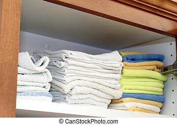 Rags on a Shelf - A variety of folded cleaning rags on a...