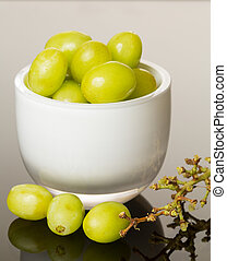 White glass bowl full of green grapes - White glass cup full...