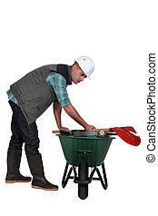 Labourer placing his tools in a wheelbarrow