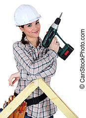 Female construction worker holding a battery-powered...
