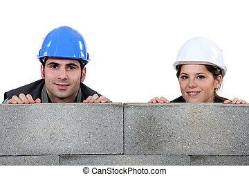 Tradespeople hiding behind cinder blocks