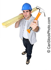 Man holding hammer and planks of wood