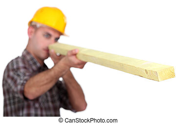 Carpenter looking down the length of a wooden plank