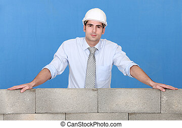 Engineer standing over a stone wall