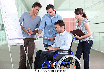 Man in wheelchair surrounded by colleagues