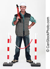 Tradesman standing in front of a barrier
