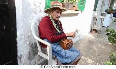 senior woman and coffee grinder - senior woman using an old...