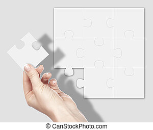 Puzzle pieces and human hand