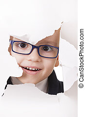 Curious kid looks through a hole in paper - Curious kid in...