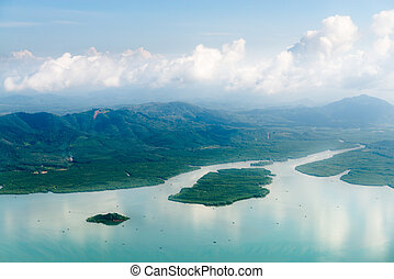 Aerial view of mangrove forests in blue water of Andaman sea