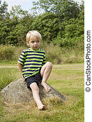 Blond young boy posing on a rock