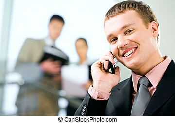 Busy man - Portrait of a young handsome businessman speaking...