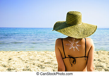 Woman on beach with sun symbol on her back - UV protection...