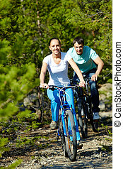 Two cyclists  - A young people riding bicycles in wood
